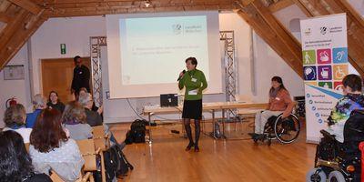 Die Vorsitzende des Behindertenbeirats Dr. Frauke Schwaiblmair spricht ein Grußwort; rechts neben ihr: die Organisatorin des Netzwerktreffens, Sigrid Karl, Beauftragte für Menschen mit Behinderung im Landkreis München.