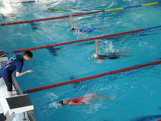 Schwimmerinnen beim Wettkampf im Rückenschwimmen.