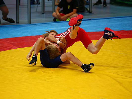 Zwei Ringer kämpfen miteinander auf der Ringermatte.