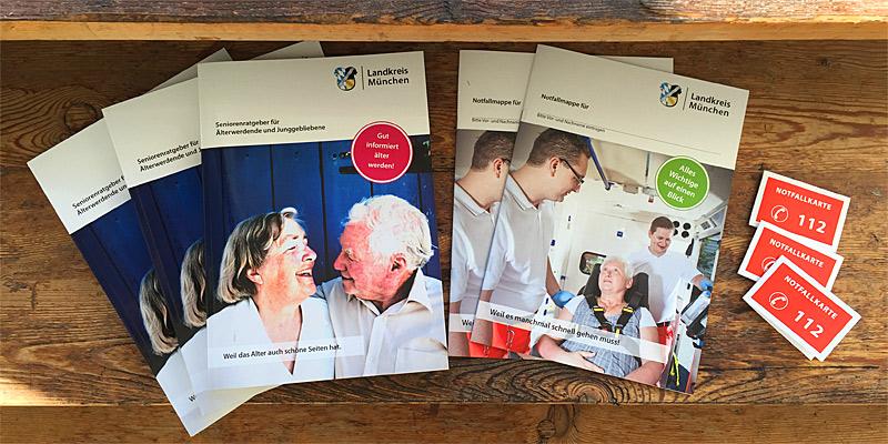 Foto: Der neue Seniorenratgeber und die Notfallmappe des Landratsamts München.